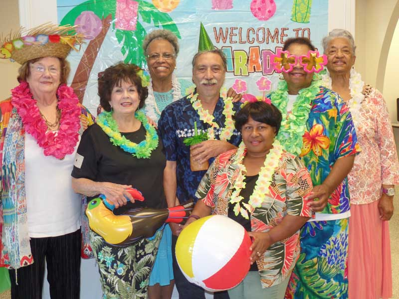 7 people pose for a tropical party photo